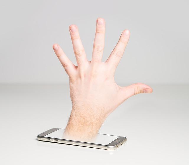 ruka a mobilní telefon