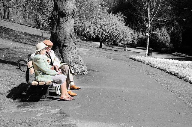 Starší manželský pár sedící na lavičce v parku